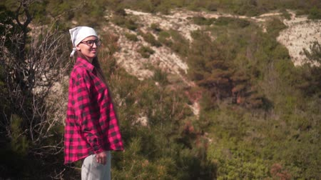 tracking : In the frame, a girl with dark hair in a black and red shirt, a bandana and glasses stands in the forest, then the frame moves to the right, revealing views of the sea, the beach, and the mountains.