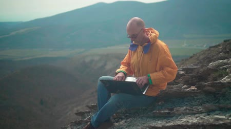 tramp : A man in a yellow jacket, blue jeans and glasses sits on the edge of a cliff and works on a laptop, he looks at the screen and types the text. In the background are hills and sky. Mountain landscape.