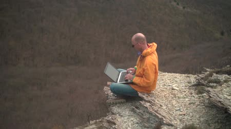 tramp : A man in a yellow jacket, blue jeans and glasses sits on the edge of a cliff and works on a laptop, he looks at the screen and types the text. In the background hills and woods. Mountain landscape.