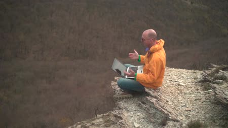 tramp : A man in a yellow jacket, blue jeans and glasses sits on the edge of a cliff and works on a laptop, then enjoys successful work. In the background are hills and woods. Mountain landscape.