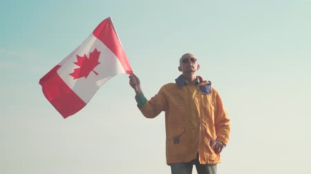canadian maple leaf : A man in the mountains stands and holds the Canadian flag on the background of mountains and sky. He is wearing bright yellow clothes and glasses. The flag of Canada is developing in the wind.