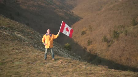 canadense : A man in the mountains holds the Canadian flag on the background of mountains and sky. He is wearing bright yellow clothes and glasses. The flag of Canada is developing in the wind. The far plan.