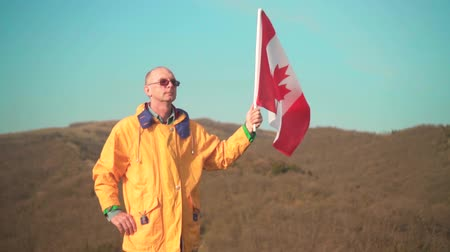 canadense : A man in the mountains stands and holds the Canadian flag on the background of mountains and sky. He is wearing bright yellow clothes and glasses. The flag of Canada is developing in the wind.
