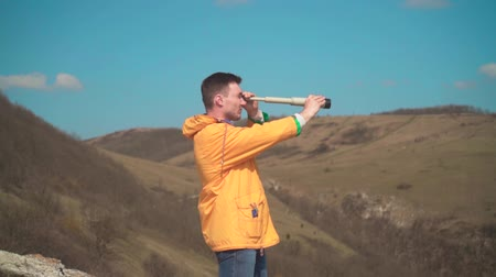 tramp : A young man in a yellow jacket, blue jeans sits on a rock and looks into a spyglass. In the background are mountains and sky. Mountain landscape. Stock Footage