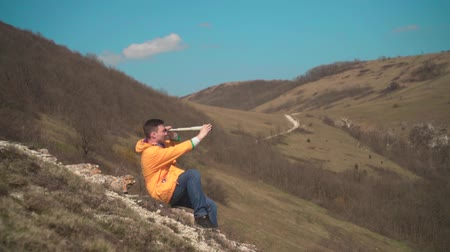 backpacken : A young man in a yellow jacket, blue jeans sits on a rock and looks into a spyglass. In the background are mountains and sky. Mountain landscape. Stockvideo