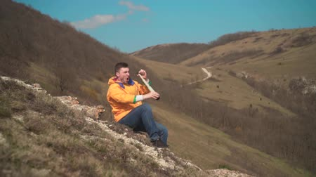 tramp : A young man in a yellow jacket, blue jeans sits in the mountains and enjoys the scenery, looking through a telescope, and then talking on the phone. In the background are hills and sky.