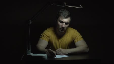 el yazması : Overall plan. A man in a yellow T-shirt works at a table in the dark. A man writes by hand with a pencil on paper.
