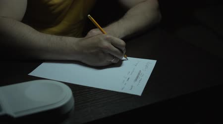 documentation : A man in a yellow T-shirt works at a table in the dark. A man writes by hand with a pencil on paper. Close-up of hands.