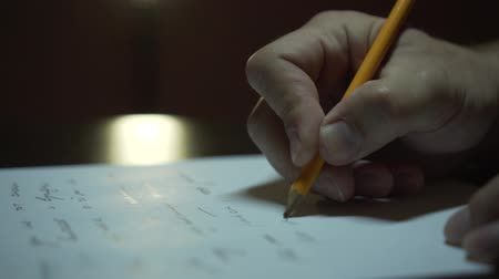 připomínka : Male hand writing on a sheet of paper in the room. Close up of a male hand writing on paper under dim light. Dostupné videozáznamy