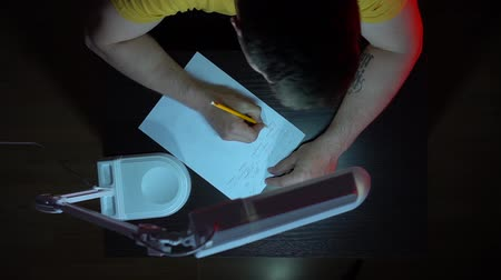 el yazması : View from above. A man in a yellow T-shirt works at a table in the dark. A man writes by hand with a pencil on paper.