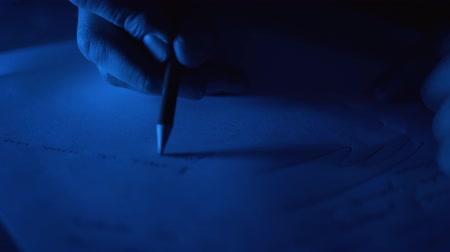 připomínka : Male hand writing on a sheet of paper in the room. Close up of a male hand writing on paper in the dark of blue light. Dostupné videozáznamy