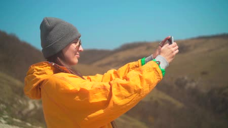tramp : A young girl with long dark hair in a yellow jacket, a gray cap and glasses is standing on the mountain and making a photo on the phone. Background mountains, sky.