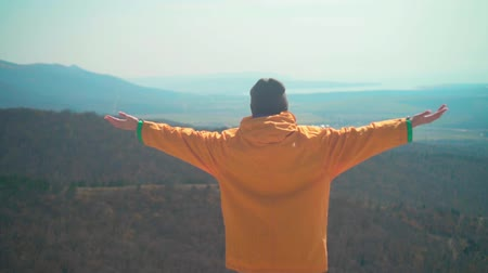 tramp : A young girl with long dark hair in a yellow jacket and a gray cap is standing on the mountain, with her back to the frame and raising her arms, as a sign of freedom. Background mountains, sky. Stock Footage