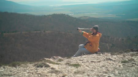 tramp : A young girl with long dark hair in a yellow jacket and a gray cap is standing in the mountains and looking through a telescope. Background mountains, sky.