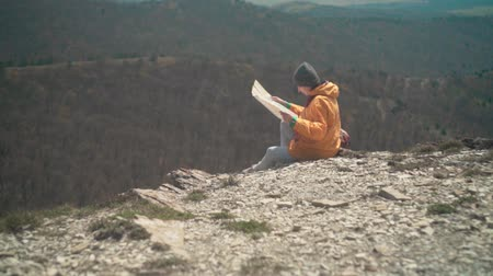 barbone : A young girl with long dark hair in a yellow jacket and a gray cap sits in the mountains and looks at a tourist map. Background mountains, sky.