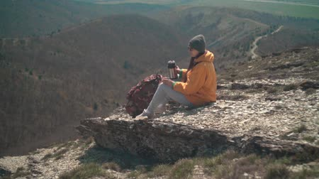 tramp : A young girl with long dark hair in a yellow jacket, a gray cap and glasses sits on a mountain, pours tea from a tumbler, then drinks. Background mountains, sky. Stock Footage