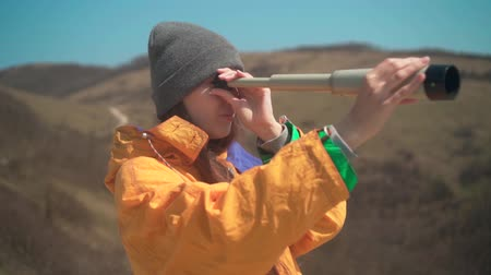 prozkoumat : A young girl with long dark hair in a yellow jacket and a gray cap is standing in the mountains and looking through a telescope. Background mountains, sky.