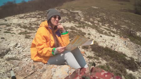 tramp : A young girl with long dark hair in a yellow jacket and a gray cap sits in the mountains and looks at a tourist map. Background mountains, sky.