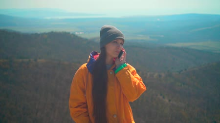 tramp : A young girl with long dark hair in a yellow jacket, a gray cap and glasses is standing on the mountain and talking on the phone. Background mountains, sky.
