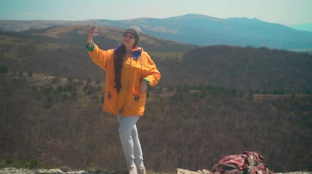 tramp : A young girl with long dark hair in a yellow jacket and a gray cap stands on a mountain and takes a selfie on the phone. Background mountains, sky.