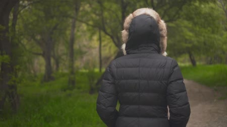 kürk : A girl in a warm black jacket walks through the woods. The girl goes in front, the camera follows her. Around the girl is green for the trees and brown tree trunks. Slow motion video. Stok Video