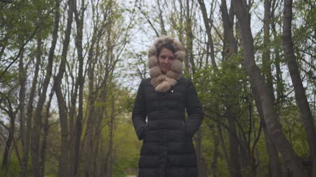 hajtások : A girl in a warm black jacket walks through the woods. The girl follows the camera shoots from top to bottom. Around the girl are green trees and brown tree trunks. Stock mozgókép