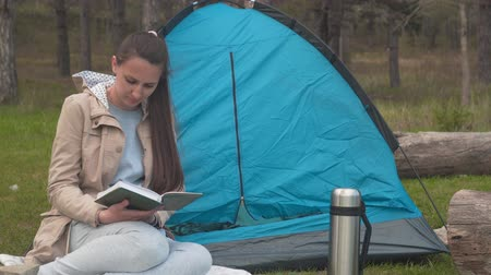 sefer : A young girl with long hair is sitting near a blue tent in the forest and reading a book. Background - pine forest. Stok Video
