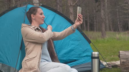 sefer : A young girl with long hair is sitting near a blue tent in the woods and talking over the video link on the phone. Background - pine forest. Stok Video