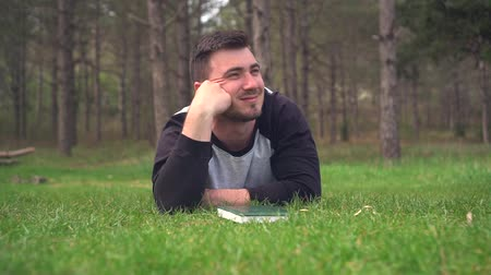 detektivní : A young guy is lying on the green grass in the forest and reading a book. Rest, relaxation, pleasure. Background - pine forest. Dostupné videozáznamy