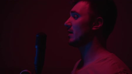 рэп : Man singing into a microphone on a dark blue-red background. Stylish cool guy with a fashionable hairstyle, singing a song with emotions. Стоковые видеозаписи