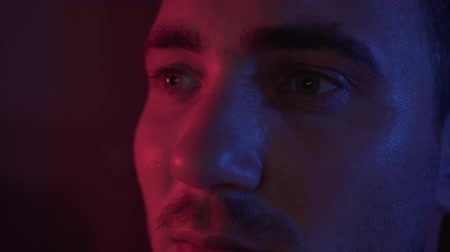Portrait of a young man with a beard and mustache, closeup view of a man. The man is an itchy serious in the blue-red light of darkness.