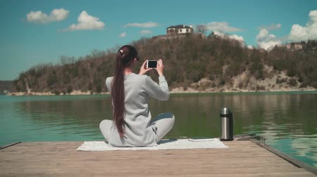 A young woman makes a photo on the phone in the sun, sitting on a wooden pier of the lake on a spring day, relaxing in nature. Girl backs in the frame. Rest, harmony with nature.