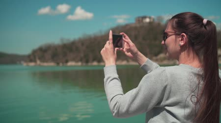 A young woman in sunglasses sits by the lake on a spring day and takes a photo on the phone, relaxing in nature. Rest, harmony with nature.