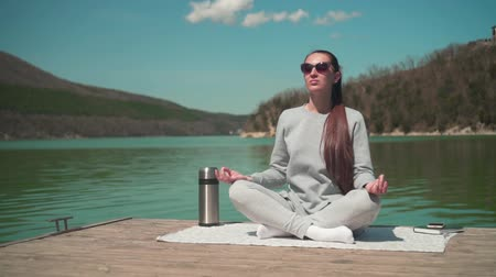 A young woman is meditating in the sun while sitting on a wooden pier of a lake on a spring day, relaxing in nature. Meditation harmony with nature. Wideo