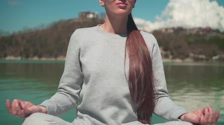A young woman is meditating in the sun while sitting on a wooden pier of a lake on a spring day, relaxing in nature. The camera goes from the bottom up. Meditation harmony with nature.