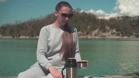 A young woman drinks tea from a thermos in the sun, sitting on a wooden pier of the lake on a spring day, relaxing in nature. Rest, harmony with nature. Wideo
