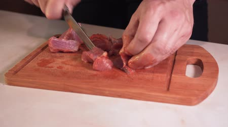 глыба : Close up shot of a mans hands cutting raw meat on a cutting board. Man prepares ingredients for cooking. Стоковые видеозаписи