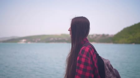 à beira do lago : Medium shot of a young attractive girl in a red plaid shirt, posing for the camera. The girl goes along the shore of the lake on a warm day. Stock Footage
