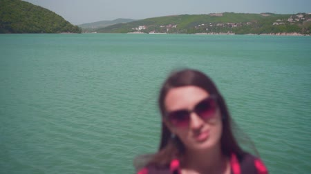 à beira do lago : Portrait of a young attractive girl in a red checkered shirt, posing in front of the camera. On a warm day, a girl stands on the shore of a lake.