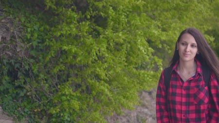 à beira do lago : Medium shot of a young attractive girl in a red checkered shirt. The girl goes on the road along the green bushes on a warm day.