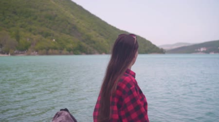 Medium shot of a young attractive girl in a red plaid shirt posing for the camera. The girl is sitting on the shore of the lake on a warm day. Wideo