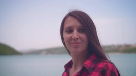macacão : Portrait of a young attractive girl in a red checkered shirt, posing in front of the camera. A girl stands on the shore of the lake on a warm day.