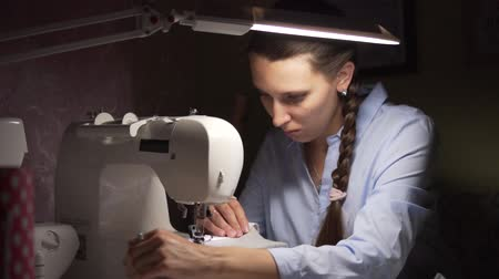 handig : Close-up of a young woman sewing on a sewing machine. A woman sews clothes on a sewing machine by the light of a lamp. Fashion, creation and tailoring. Stockvideo