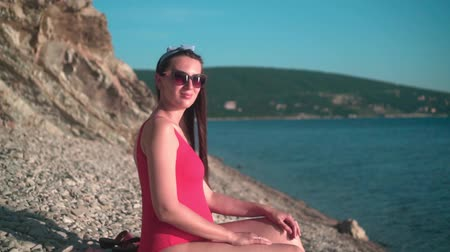 Beautiful pregnant girl in a red one-piece swimsuit and glasses sits on the beach. Mountains in the background. Wideo