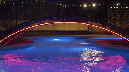 Pool with night lighting, which changes color. Outdoor pool with cold water. Night swimming pool with lighting. Changing colorful lights in the night pool. Stock mozgókép