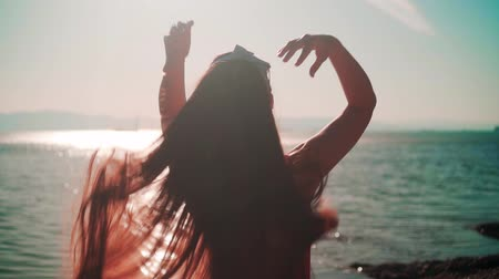 A beautiful young girl in a red one-piece swimsuit and glasses stands on the seashore in the rays of the sunset sun. The girl touches her hair, blowing in the wind. Girl backs in the frame. Wideo