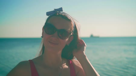 A beautiful young girl in a red one-piece swimsuit and glasses stands on the seashore in the rays of the sunset sun. Sun Overexposure Effect