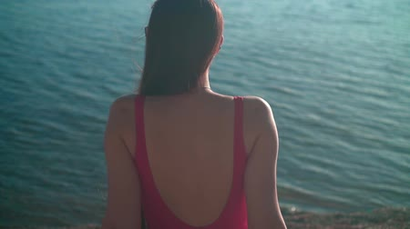 A beautiful young girl in a red one-piece swimsuit sits on the seashore in the sunset sun. The girl sits back in the frame.