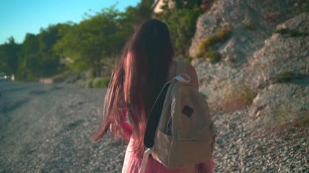 A beautiful young girl in a red one-piece swimsuit and glasses walks along the seashore in the rays of the setting sun, on her shoulder a beige backpack, a girl with her back in the frame. Wideo