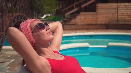 A beautiful pregnant girl in a red one-piece swimsuit and glasses is lying on a lounger with her hands under her head near the pool. Wideo